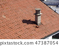 A close up view of a chimney on top of red roof tiles 47387054