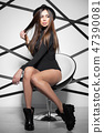 Perfect woman sits on a chair in the studio. 47390081