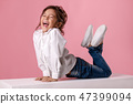 Cute happy laughing little girl in white shirt with hairstyle 47399094