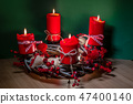 Modern Christmas wreath with four red candles on wooden surface with green background 47400140