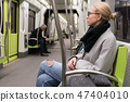 Beautiful blond woman wearing winter coat and scarf traveling by metro. Public transport. 47404010