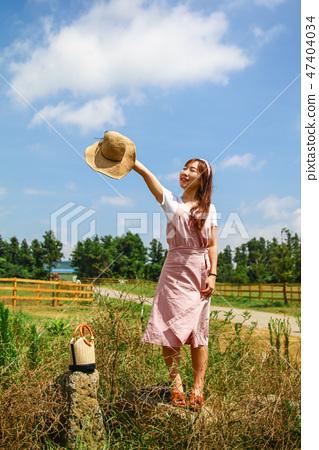 파란 하늘을 향해 모자를든 손을 뻗고 있는 여성 여행자 47404034