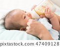 Hand of mother feeding baby with milk bottle 47409128