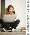 Young woman laughing at her smartphone 47418715