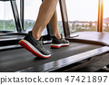 Male feet in sneakers running on the treadmill 47421897