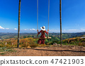 Young woman sitting on a swing 47421903