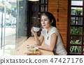 Asian woman hands holding coffee mug 47427176
