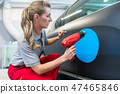 Woman putting sticker with company slogan on a car 47465846
