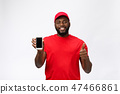 Delivery Concept - Portrait of Happy African American delivery man in red cloth holding a box 47466861