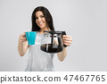young girl with a coffee pot and a mug stands isolated on a light background 47467765