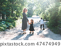 A woman walking with her children on the road 47474949