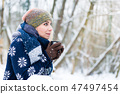 Woman freezing on a cold winter day warming herself up with hot drink 47497454