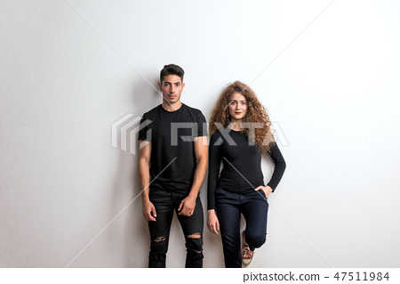 Portrait of a young couple standing in a studio, wearing black clothes. 47511984