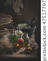Essential oil bottles, mortar, books, dry roots. 47517797