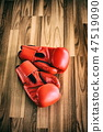 Red boxing gloves on a wood background. 47519090