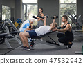 Man lying on bench working out, people training. 47532942