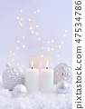 Christmas candles on the snow and Christmas lights 47534786