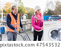 Woman and man giving electrical appliances to recycling center 47543532