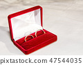Two golden wedding rings on the white fabric.  47544035