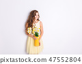 A studio shot of a girl standing and holding a 47552804