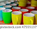 Many colored mugs in the store 47555137