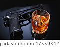 Glass of whiskey or cognac, gun, playing cards with money on the black mirror table. The concept of 47559342
