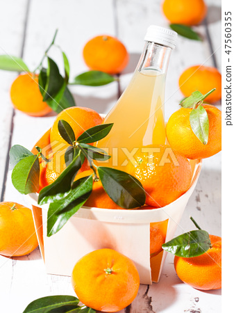 Glass bottle of fresh mandarin tangerine juice 47560355