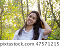 Portrait of asian college woman smiling in blur background witn sunset. 47571215