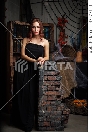 Beautiful young woman in black dress indoor 47577111