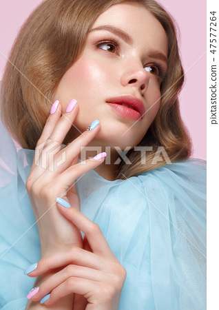 Beautiful girl with light make-up and gentle manicure in blue clothes. Beauty face. Design nails. 47577264