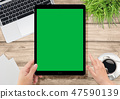 Human hand holding tablet with green screen 47590139