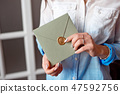Close-up woman with slim body holding in hands the invitation card gray-green color square shape 47592756