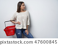 Woman holding empty shopping basket looking aside 47600845