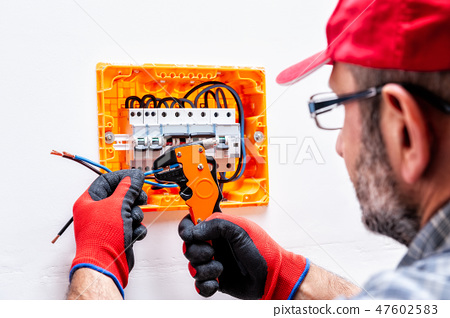 Electrician at work on an electrical panel. 47602583