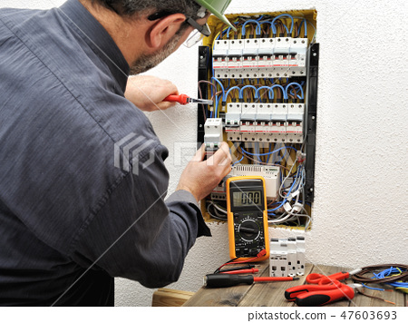 Electrician at work on an electrical panel 47603693