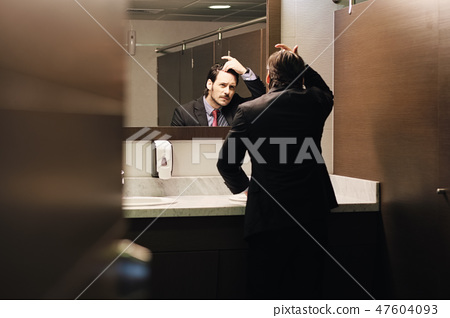 Worried Hispanic Business Man Looking At Hairline In Office Restrooms 47604093