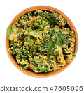 Homemade kale chips in wooden bowl over white 47605096