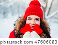 Beautiful young woman holding a red heart in the hands in winter park. Winter time. 47606083