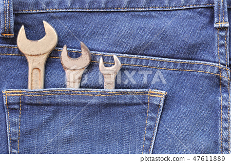 Blue jeans of back pocket and have old wrench tool with rust. 47611889
