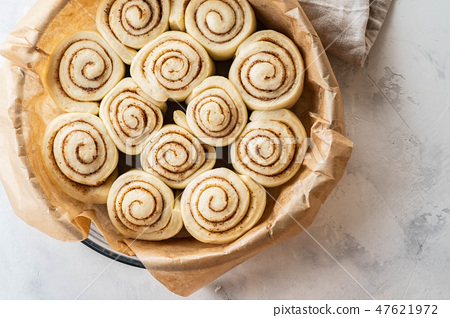 Raw cinnamon rolls in baking plate on kitchen table. Copy space. 47621972