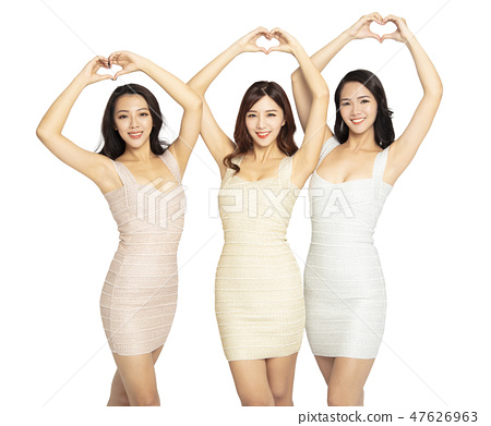 three young Woman showing Heart Shaped gesture 47626963