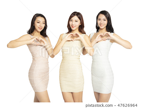 three young Woman showing Heart Shaped gesture 47626964