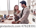 Pretty long-haired young woman in a white shirt and her husband enjoying breakfast 47628391
