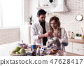 Dark-haired bearded young man in a white t-shirt hugging his blond long-haired wife 47628417