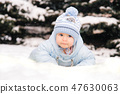 A small child in a blue overalls lying on the snow near the Christmas trees 47630063
