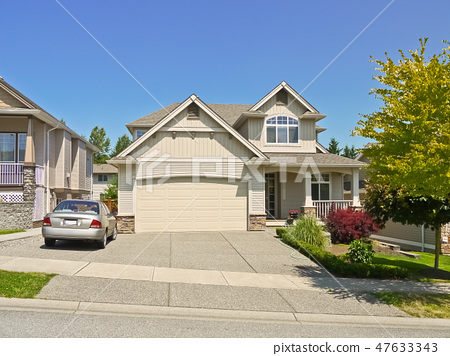 Luxury family house with a car parked on concrete driveway in front 47633343