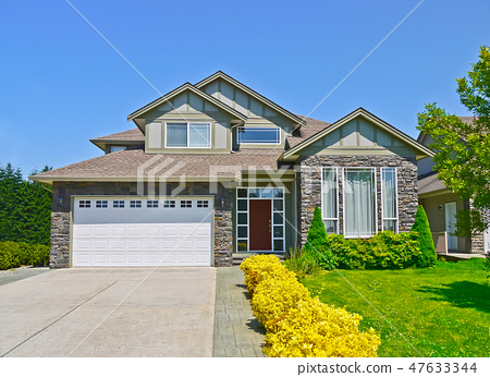 Luxury family house with concrete driveway to the garage on blue sky background 47633344