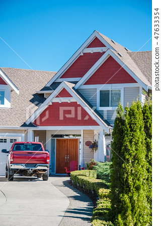 Red luxury residential house with red truck in front of the entrance 47633354