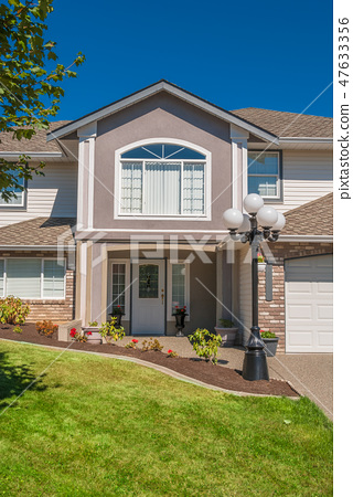 Main entrance of luxury house with flowerbed and grass lawn in front 47633356
