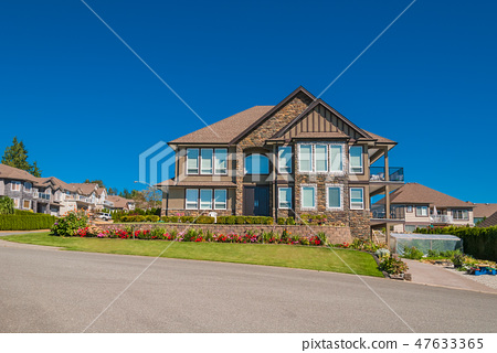 Luxury house in the center of neighbourhood with flowers on the front yard 47633365